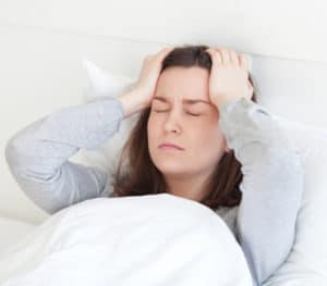 Young woman lying sick in bed having headache